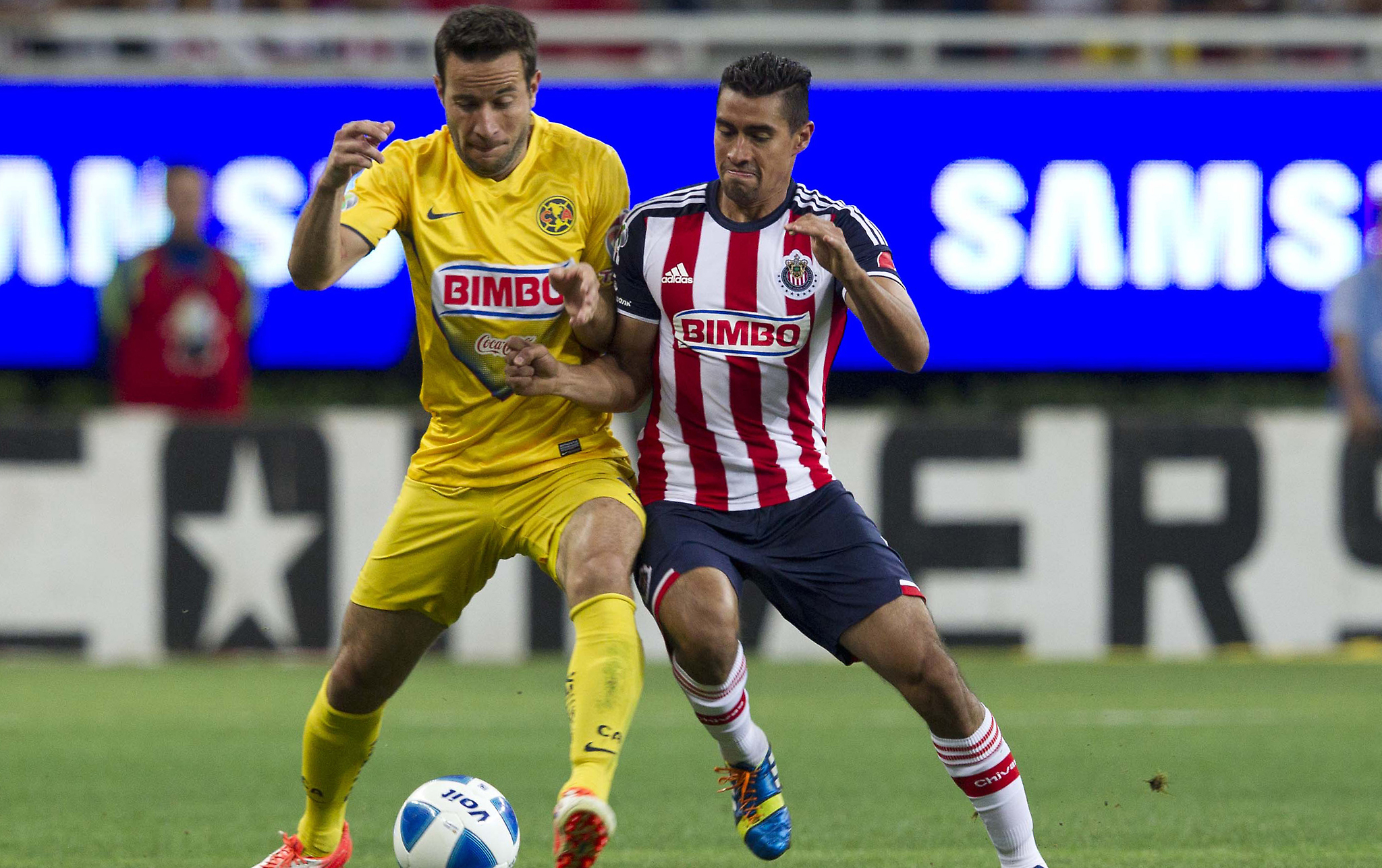Chivas de Guadalajara's Patricio Araujo, right, fights for the ball with America's Gabriel Rey during a Mexican soccer league match in Guadalajara, Sunday, March 30, 2014. (AP Photo/Refugio Ruiz) ORG XMIT: MXRR107